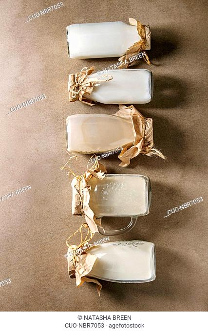 Variety of non-dairy vegan lactose free nuts and grain milk almond, hazelnut, coconut, rice, oat in glass bottles in row over brown texture background