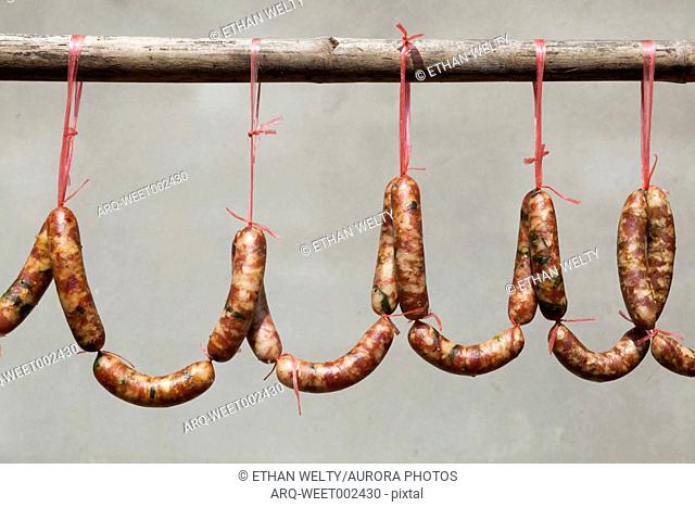Seasoned and cured pork sausages hang for sale in the streets of Muang Ngoi, Laos