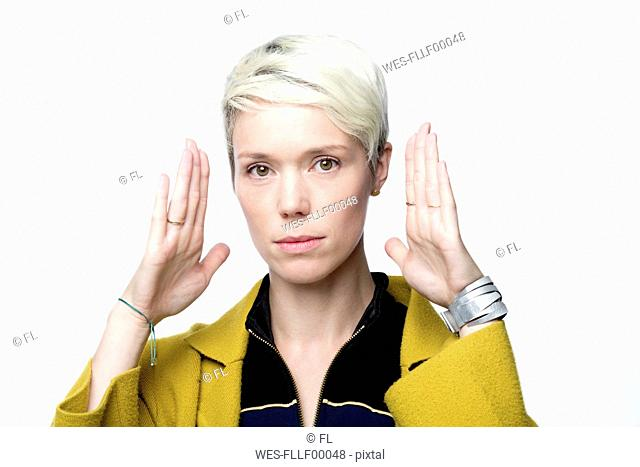 Portrait of woman with short blond dyed hair in front of white background gesturing