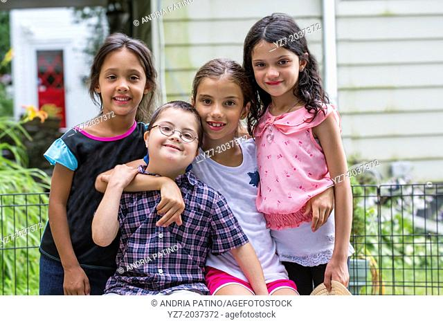 Four cousins ages 6-9 years old hugging and posing for camera