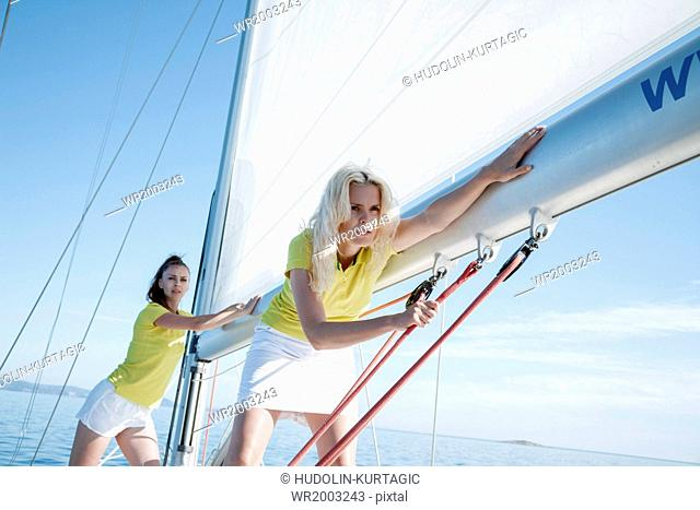 Two women adjusting rigging together on sailboat, Adriatic Sea