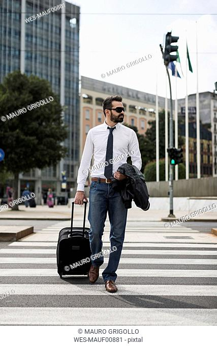 Businessman with suitcase crossing the street