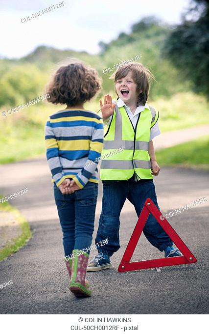 Boy playing traffic worker on rural road