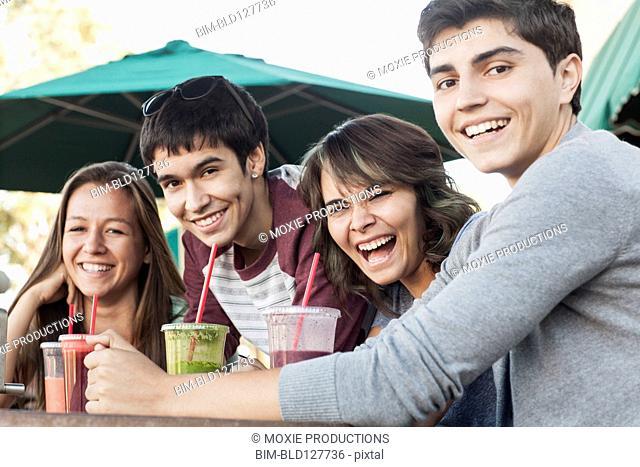 Teenagers drinking smoothies at sidewalk cafe