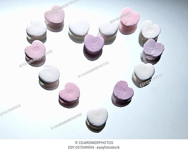 A collection of heart shaped candies form a larger heart shape on a light background