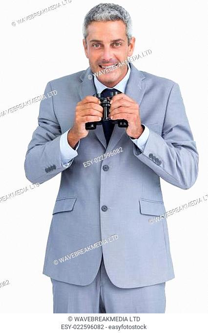 Businessman holding binoculars in both hands