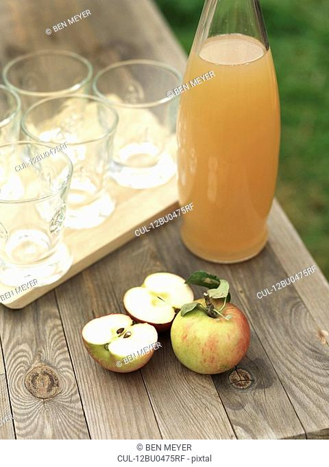 Apples, apple juice and glasses on table