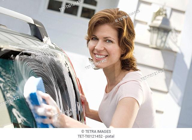 Woman washing car in driveway