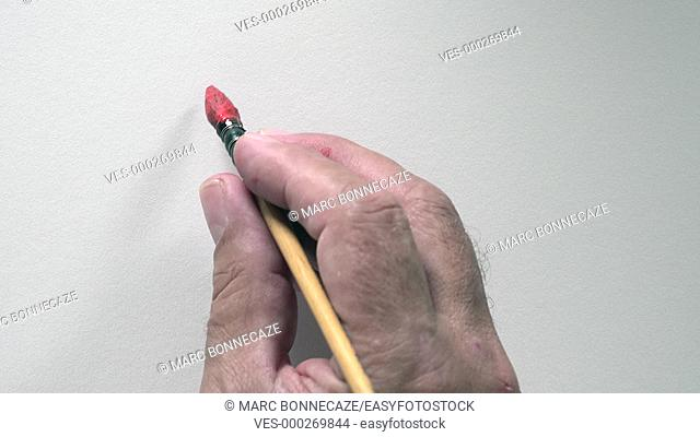 Human hand writing word BONNE ANNEE in french, with red gouache