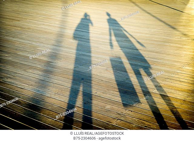 Shadow of the silhouette of a photographer taking a picture to a woman with a shopping bag, in Tel Aviv Harbour, Israel, Middle East