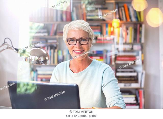 Businesswoman smiling at computer in home office