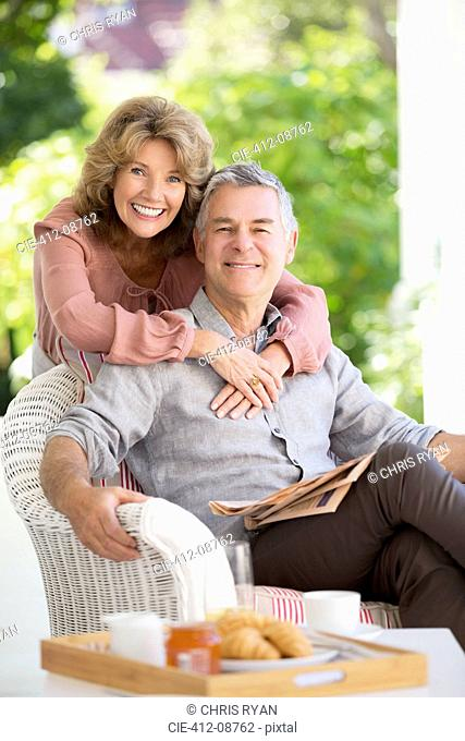 Portrait of smiling senior couple hugging on patio
