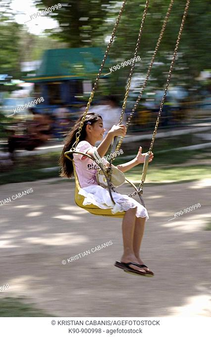 Kid on a merry-go-round (chairoplane)l in the Samani amusement park, Bukhara, Uzbekistan, Central Asia