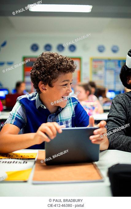 Happy elementary school boy using digital tablet in classroom