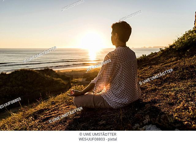 Back view of woman meditating at sunset