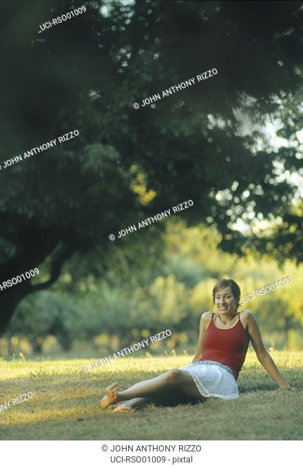 Woman relaxing on dry lawn