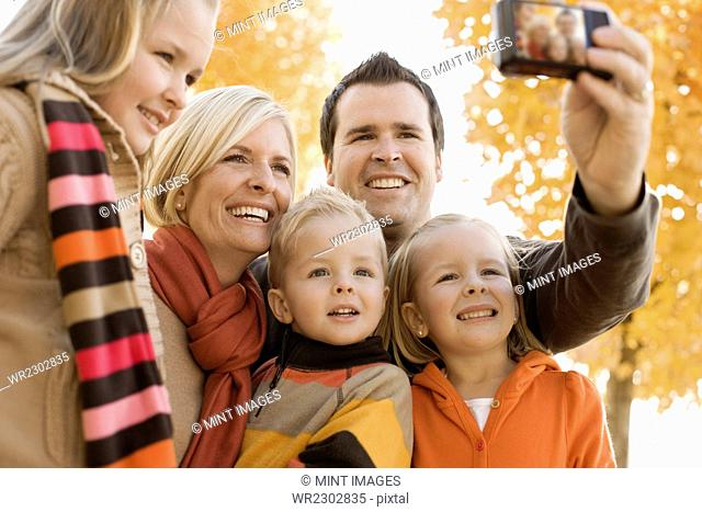 A family of two parents and three children posing for a selfy under the autumn leaves on the trees