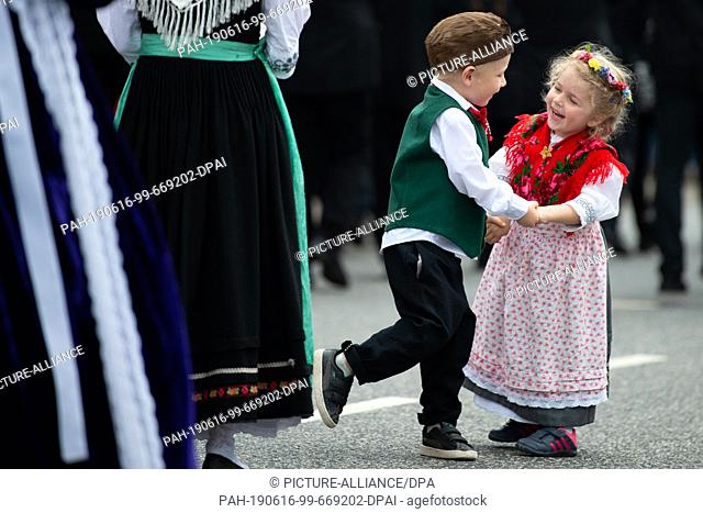"""16 June 2019, Hessen, Bad Hersfeld: Two children of the traditional costume group """"""""Folklore-Gruppe-Friedewald"""""""" dance at the big parade on the 59th Hessentag"""
