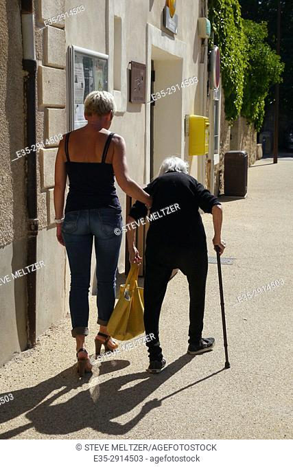 A young woman helps an elderly lady