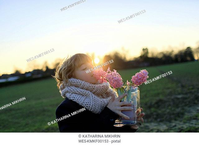 Boy on a meadow smelling hyacinth at sunset