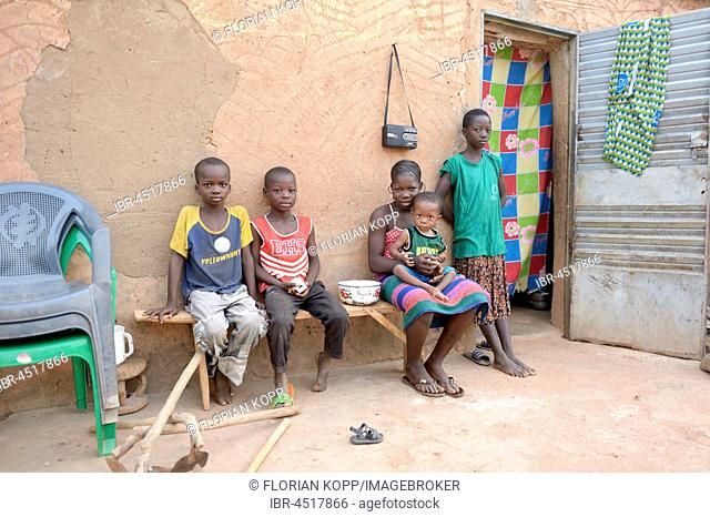 Children sitting on a bench in front of house, Toeghin village, Oubritenga province, Plateau Central region, Burkina Faso