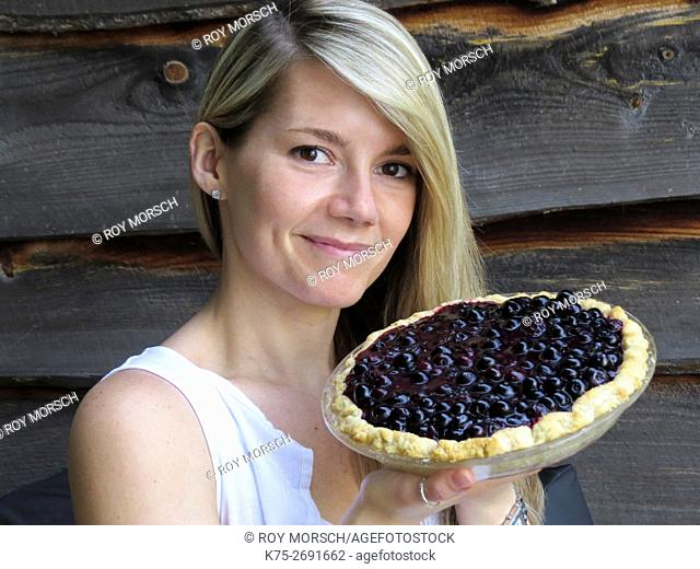 Young woman holding homemade blueberry pie