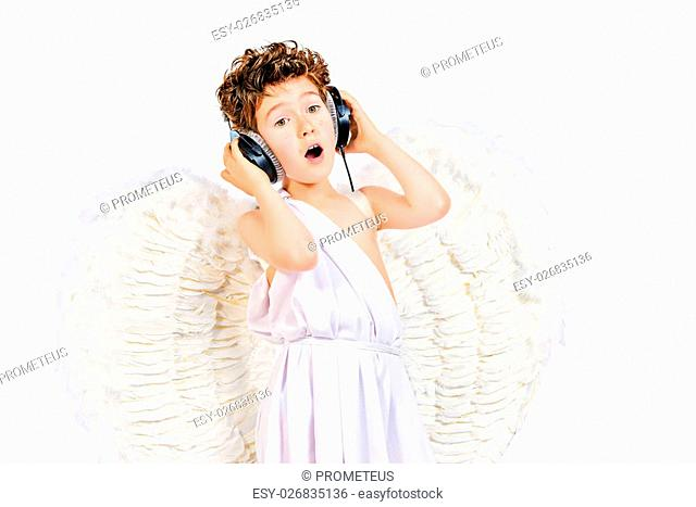 Happy little boy in a costume of angel listening to music in headphones. Cupid. Valentine's day