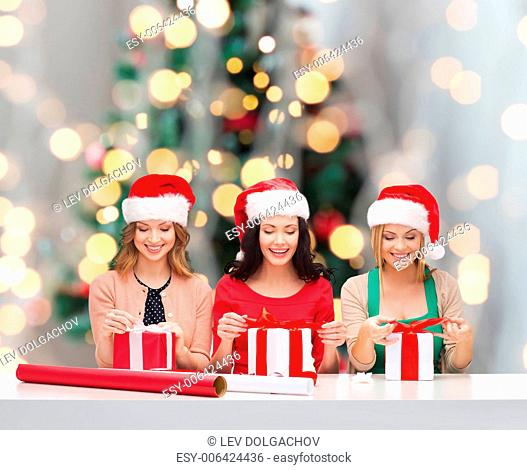 christmas, holidays, celebration, decoration and people concept - smiling women in santa helper hats with decorating paper and gift boxes over tree lights...