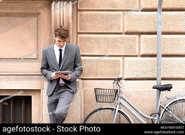 Young businessman leaning at facade looking at digital tablet