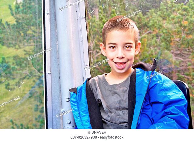 Portrait of a cut 7 year old boy having fun in a cable car while touring the Spanish Pyrenees