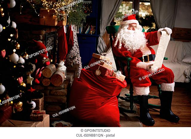 Portrait of Santa Claus, sitting in chair with sack full of presents, looking at Christmas list