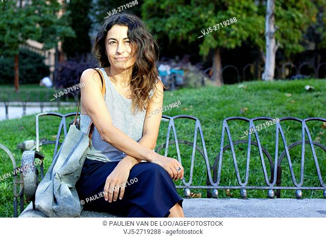 Madrid, Spain, woman relaxing, sitting on a bench at Plaza Espana in Madrid. She's a spanish english translator and has her own business