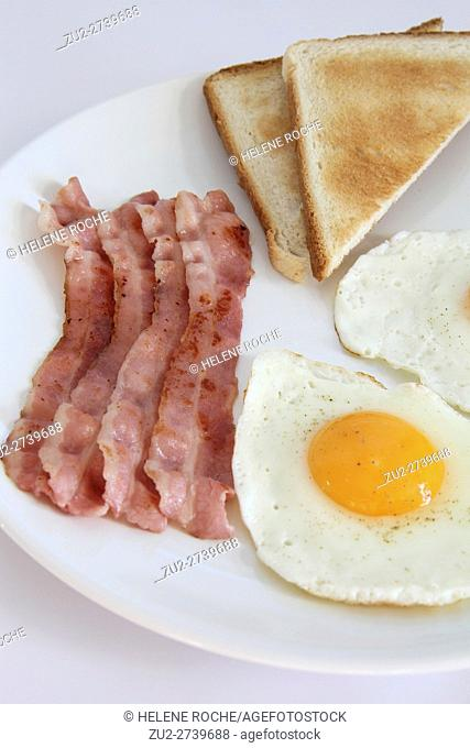 Breakfast with eggs, bacon and toasts