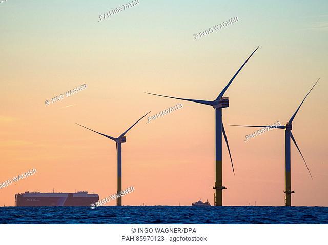 Ein Autotransportschiff passiert am 24.11.2015 im Abendlicht einige der Windkrafträder des Offshore-Windparks «Nordergründe» vor dem Sielhafen von Dorum...