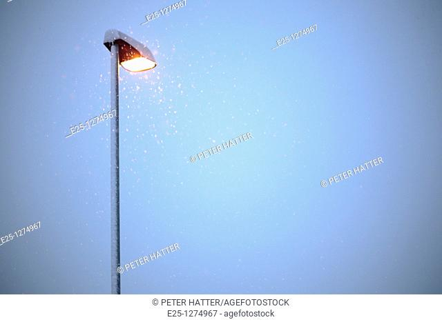 Snow falls past an illuminated street lamp in winter