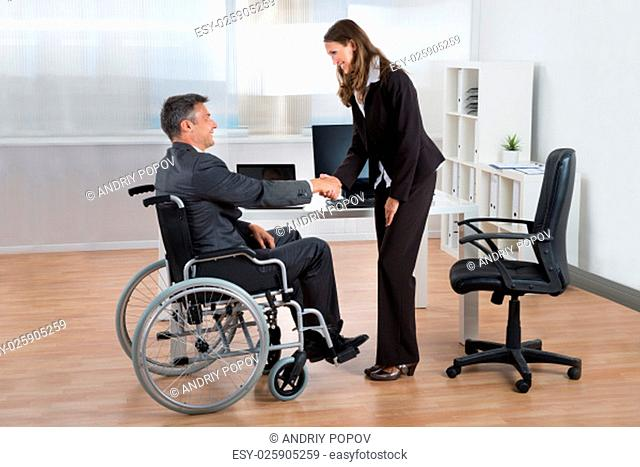 Happy Businesswoman Shaking Hands With Businessman On Wheelchair In Office