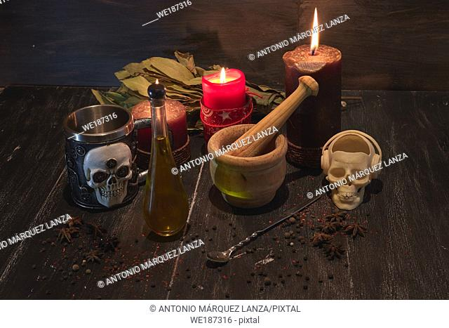 potion of natural herbs for black magic with a skull incense burner, a mortar , candle and skull metal glass