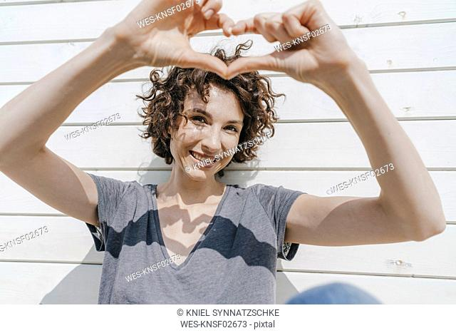 Happy woman shaping heart with her hands