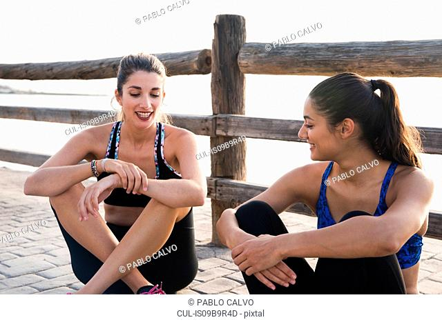 Two young women training on waterfront, sitting chatting