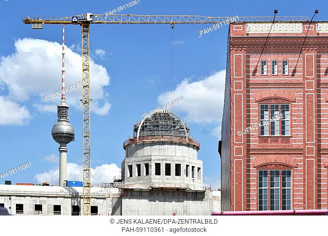 The tower cupola of the new Berlin City Palace (L), which has been named Humboldt-Forum, is pictured next to the facade of the Schinkelsche Bauakademie (lit