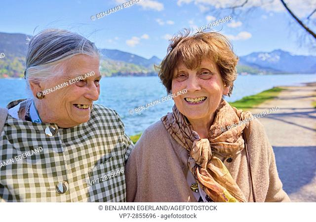 Happy two senior woman laughing together at lake Tegernsee, Bavaria, Germany