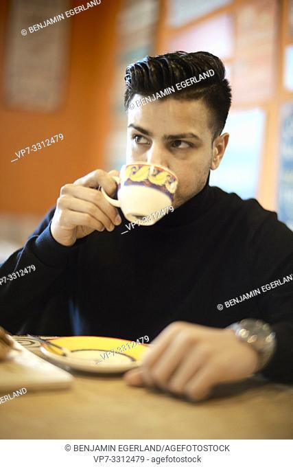young man drinking tea in café, taking break, in Munich, Germany