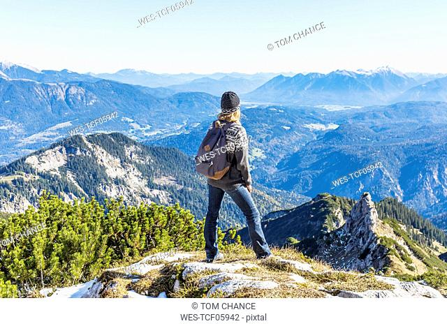 Germany, Garmisch-Partenkirchen, Alpspitze, Osterfelderkopf, female hiker on viewpoint looking at view