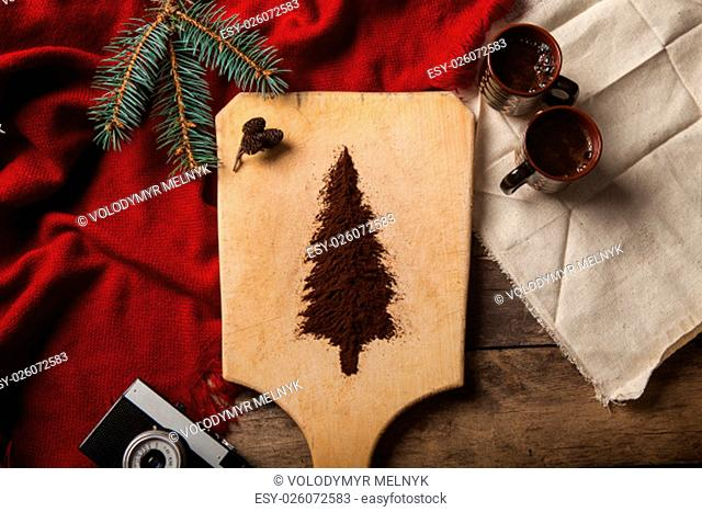 The two cups of coffee on wooden background and christmas tree made of ground coffee on a cutting board