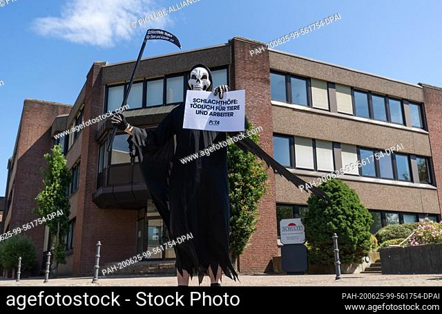 25 June 2020, Lower Saxony, Dissen: An activist of the animal protection organization Peta disguised as death stands in front of the building of the meat and...