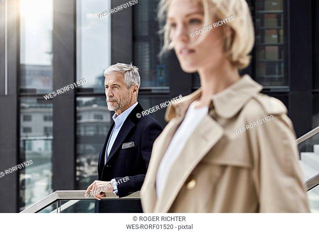 Germany, Duesseldorf, portrait of mature businessman on stairs looking at distance