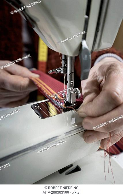 Senior female fashion designer stitching in workshop, Bavaria, Germany