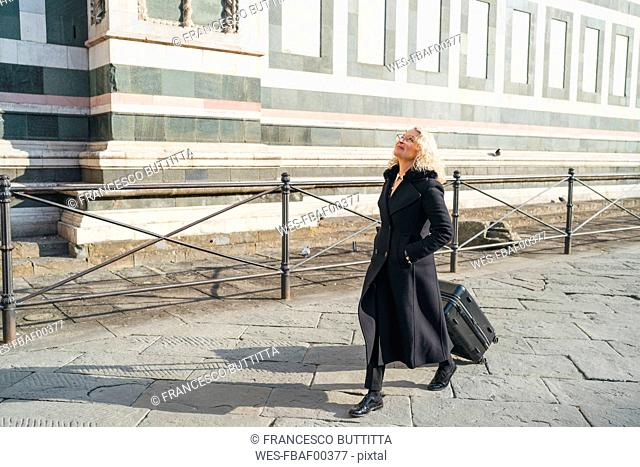 Italy, Florence, mature businesswoman wearing black coat walking in the city with rolling suitcase