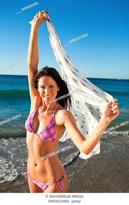 Portrait of an smiling woman raising her sarong in the air