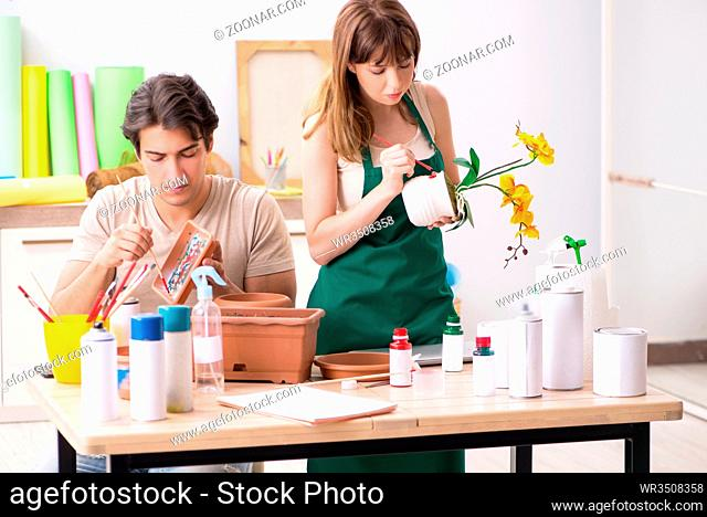 Couple decorating pots in workshop during class